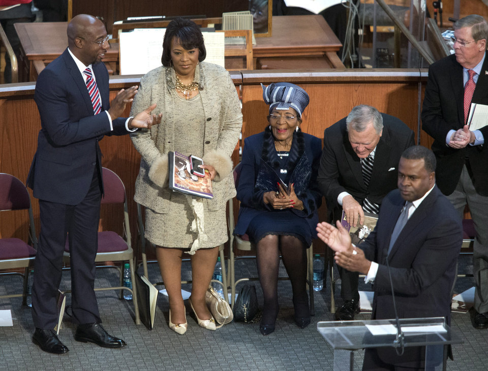 Photo - Bernice King, second from left, is honored by Atlanta mayor Kasim Reed, lower right, for her speech earlier during the Rev. Martin Luther King Jr. holiday commemorative service at Ebenezer Baptist Church Monday, Jan. 20, 2014, in Atlanta. Bernice King is the daughter of the late Dr. Martin Luther King Jr.. (AP Photo/Jason Getz)