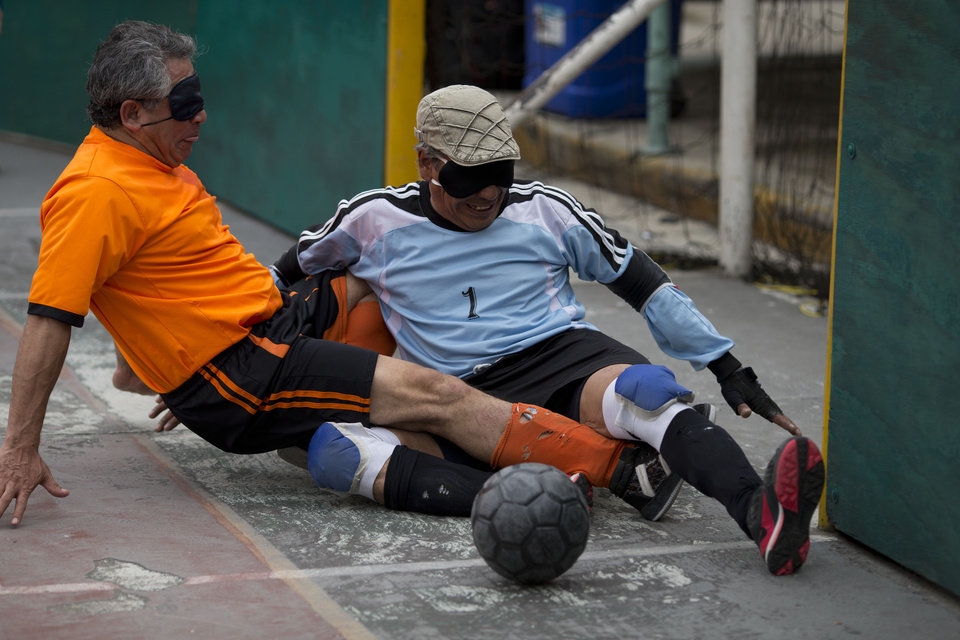 """Photo - In this Sunday, June 8, 2014 photo, Italia's goalkeeper Miguel Angel Canela stops a scoring attempt by Marco Antonio Camarillo of Leones Negros, during the league final in Mexico City. Following the match, Canela was recognized with the 2014 trophy for best goalie. Camarillo, 53, was pleased with his performance as well, after scoring one goal in the final. His wife came out to watch him play. """"She is afraid of me being hit, or falling, but she shares my love of football,"""" says Camarillo. (AP Photo/Rebecca Blackwell)"""
