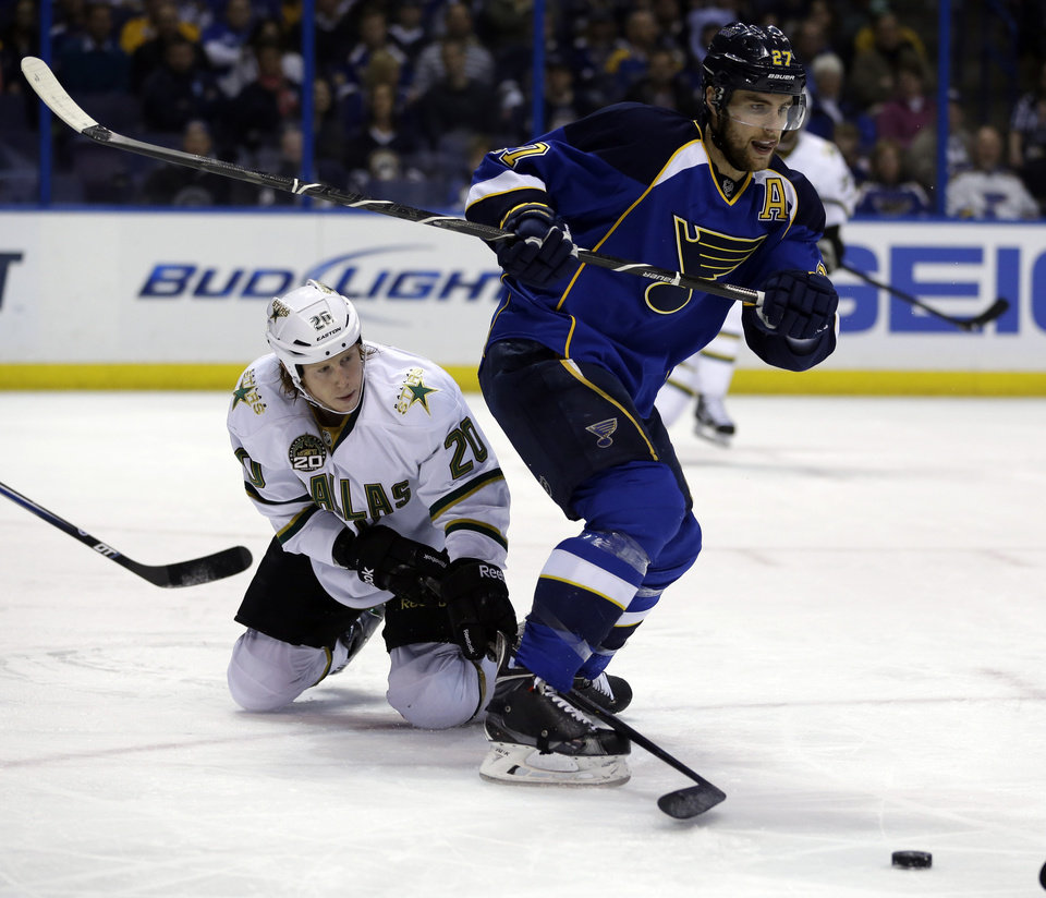 Photo - Dallas Stars' Cody Eakin, left, reaches between the legs of St. Louis Blues' Alex Pietrangelo for a loose puck the during the first period of an NHL hockey game on Friday, April 19, 2013, in St. Louis. (AP Photo/Jeff Roberson)