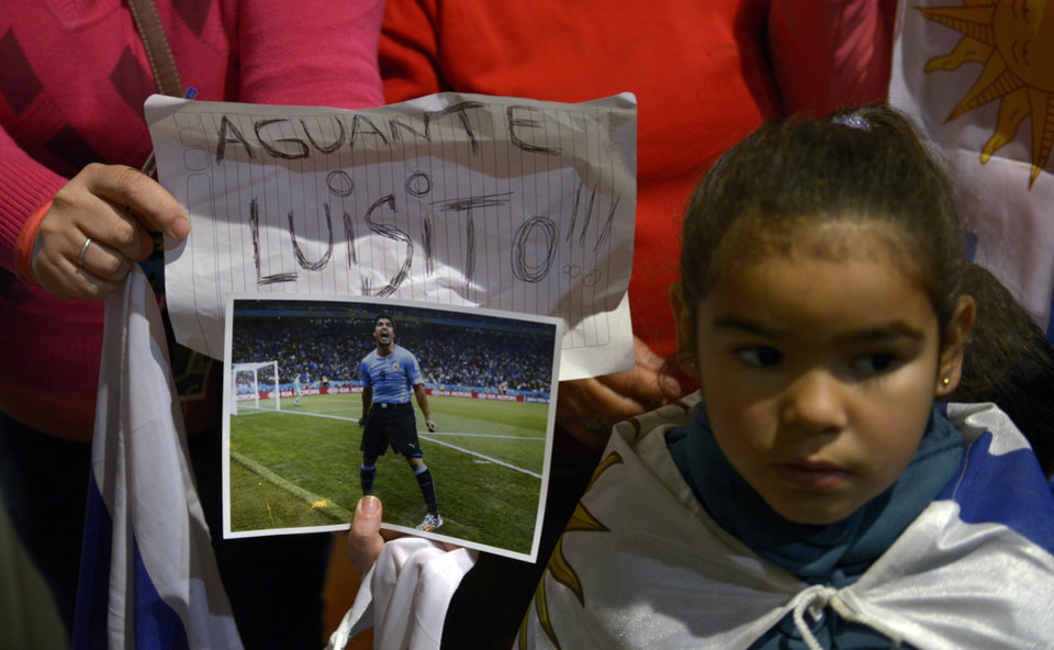 Photo - Fans of Uruguay's national soccer team await for the arrival of Uruguay player Luis Suarez with a sign that reads in Spanish