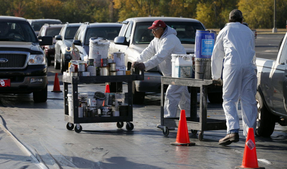 Workers unload paint cans from vehicles Saturday during the city's Household Hazardous Waste Event at the Lloyd Noble Center in Norman. PHOTO BY STEVE SISNEY, THE OKLAHOMAN <strong>STEVE SISNEY</strong>