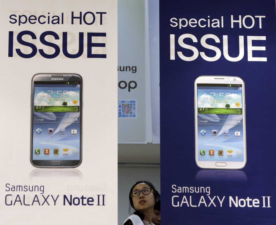 A woman tours near the billboards of Samsung Electronics's Galaxy Note II at a showroom of its headquarters in Seoul, South Korea, Friday, Oct. 5, 2012. Samsung Electronics Co. tipped all-time high quarterly operating profit, likely driven by strong sales of high-end smartphones that offset weak semiconductor orders. (AP Photo/Lee Jin-man)