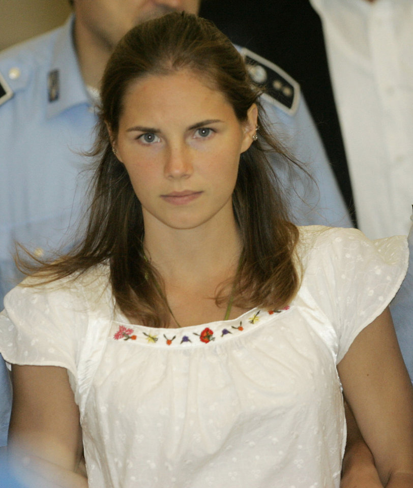 Photo - FILE - In this Tuesday Sept. 16, 2008 file photo, then murder suspect Amanda Knox is escorted by Italian penitentiary police officers from Perugia's court after a hearing, central Italy. Few international criminal cases have cleaved along national biases as that of American student Amanda Knox, awaiting half world away her third Italian court verdict in the 2007 slaying of her British roommate, 21-year-old Meredith Kercher. Whatever is decided this week, the protracted legal battle that has grabbed global headlines and polarized trial-watchers in three nations probably won't end in Florence. With the first two trials producing flip-flop guilty-then-innocent verdicts against Knox and her former Italian boyfriend, Raffaele Sollecito, the case has produced harshly clashing versions of events. A Florence appeals panel designated by Italy's supreme court to address errors in the appeals acquittal is set to deliberate Thursday, Jan. 30, 2014, with a verdict expected later in the day .(AP Photo/Antonio Calanni, File)