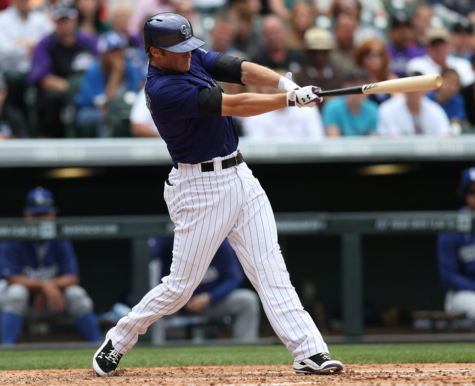 Photo - Colorado Rockies' Josh Rutledge follows the flight of his RBI-single against the Los Angeles Dodgers in the fifth inning of a baseball game in Denver on Saturday, June 7, 2014. (AP Photo/David Zalubowski)