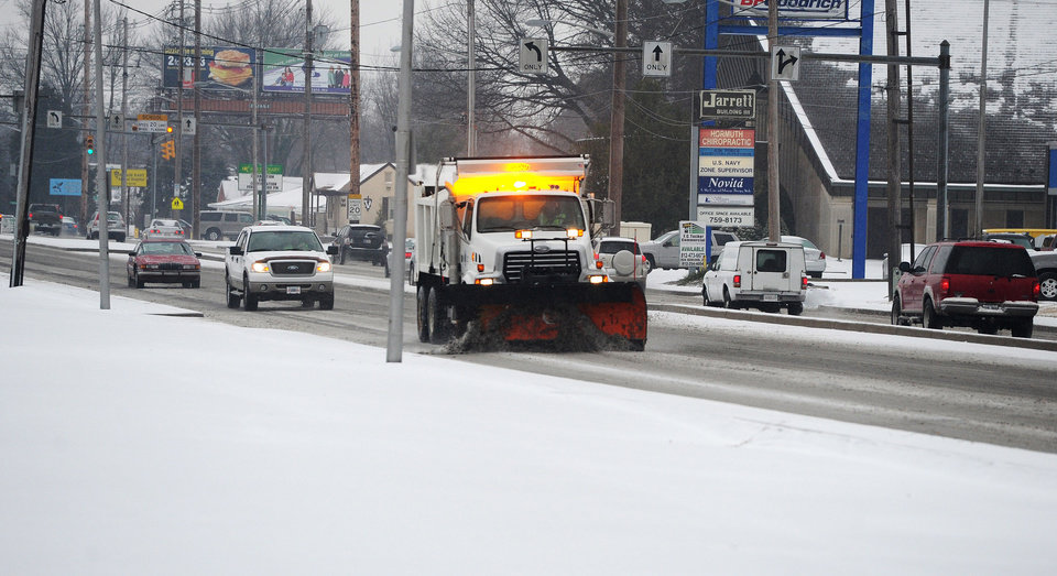 Photo - A city maintenance truck is used to remove snow and apply treatment along Green River Road in Evansville, Ind., Tuesday, Feb. 4, 2014.  A Winter Storm Warning was issued Tuesday as a mixture of snow, sleet and rain continued into the evening with temperatures around 30 degrees. (AP Photo/The Evansville Courier & Press, Jason Clark)