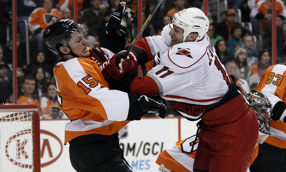 Philadelphia Flyers' Tye McGinn, left, and Carolina Hurricanes' Jordan Stall engage in a shoving match in the first period of an NHL hockey game on Saturday, Feb. 2, 2013, in Philadelphia. (AP Photo/Tom Mihalek)
