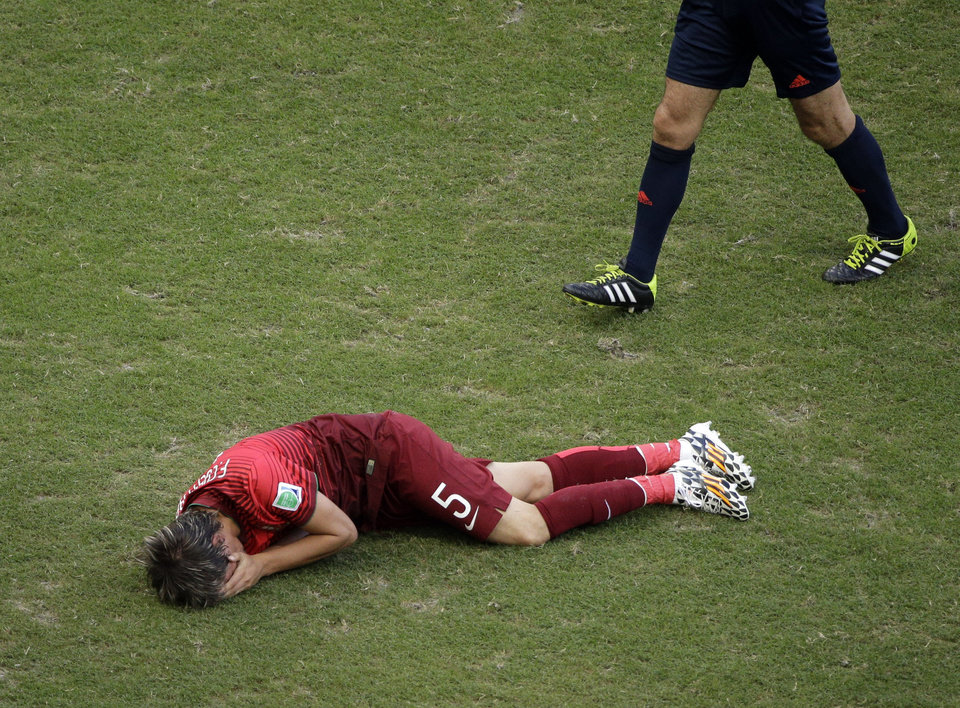 Photo - Portugal's Fabio Coentrao grimaces in pain after being injured during the group G World Cup soccer match between Germany and Portugal at the Arena Fonte Nova in Salvador, Brazil, Monday, June 16, 2014.  (AP Photo/Christophe Ena)