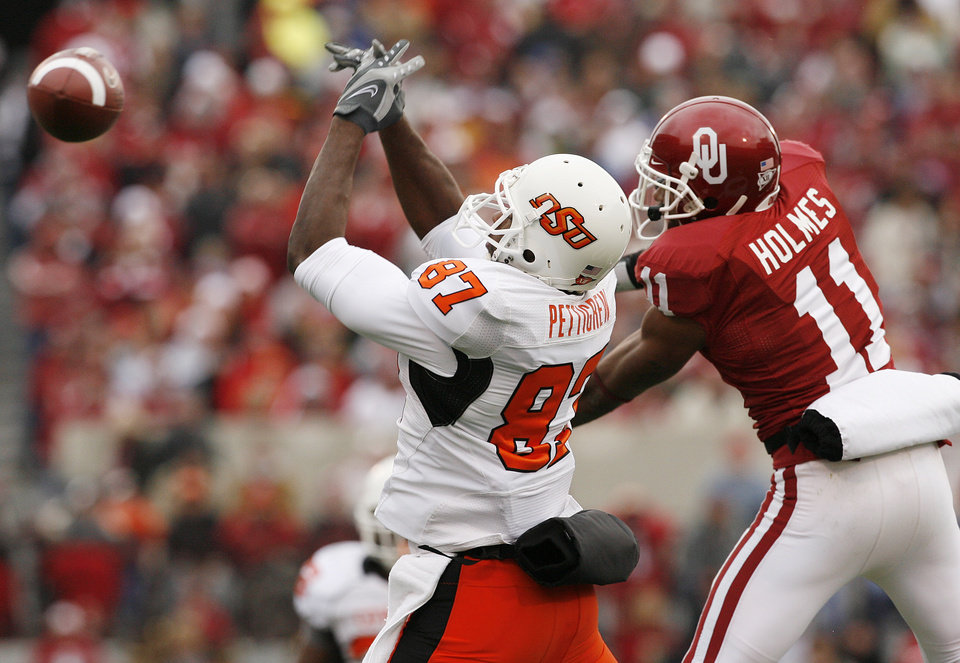 Photo - Oklahoma's Lendy Holmes (11) breaks up a pass for Oklahoma State's Brandon Pettigrew (87) during the first half of the college football game between the University of Oklahoma Sooners (OU) and the Oklahoma State University Cowboys (OSU) at the Gaylord Family-Memorial Stadium on Saturday, Nov. 24, 2007, in Norman, Okla. 