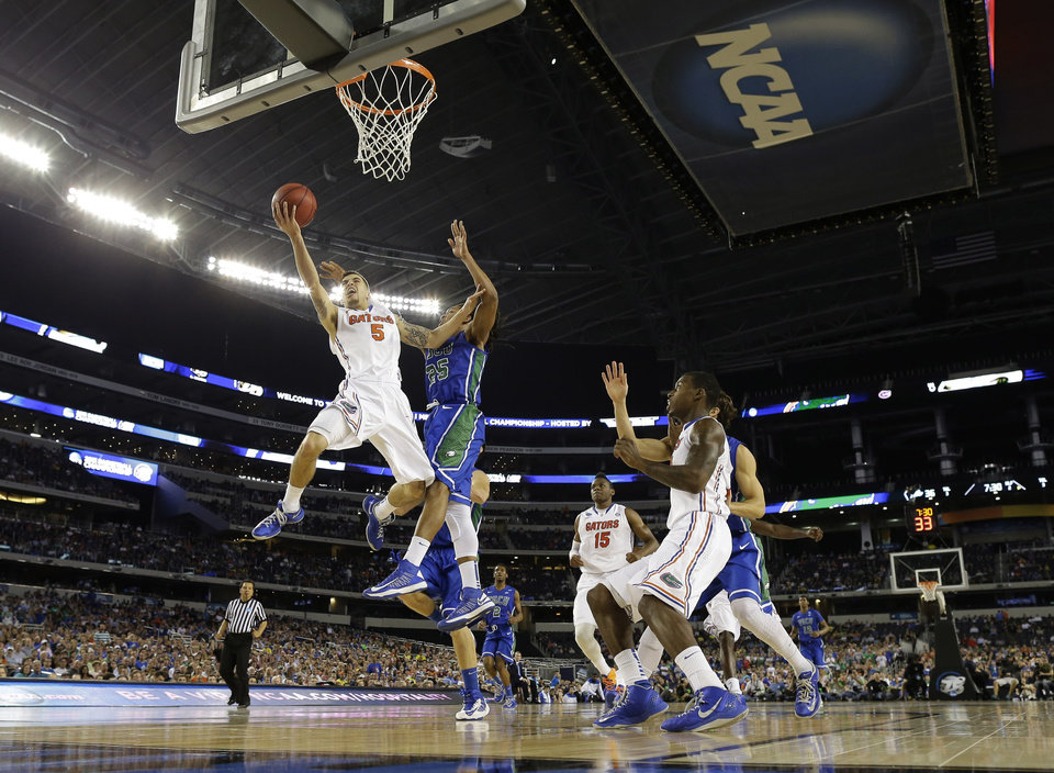 Photo - Florida's Scottie Wilbekin (5) shoots as Florida Gulf Coast's Sherwood Brown (25) defends during the second half of a regional semifinal game in the NCAA college basketball tournament, Saturday, March 30, 2013, in Arlington, Texas. (AP Photo/Tony Gutierrez)