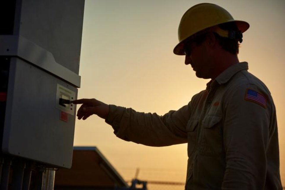 Photo -  An Oklahoma Gas and Electric Co. employee checks settings on equipment at one of the utility's power generating stations. [OGE ENERGY]