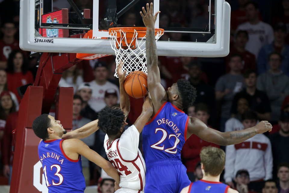 Photo - Oklahoma's Jamal Bieniemy (24) is fouled as he goes between Kansas' Tristan Enaruna (13) and Silvio De Sousa (22) during an NCAA college basketball game between the University of Oklahoma Sooners (OU) and the University of Kansas Jayhawks at Lloyd Noble Center in Norman, Okla., Tuesday, Jan. 14, 2020. [Bryan Terry/The Oklahoman]