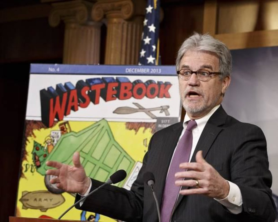 FILE - In this Dec. 17, 2013 file photo, Sen. Tom Coburn, R-Okla., a longtime deficit hawk, outlines his annual �Wastebook,� which points a critical finger at billions of dollars in questionable government spending during a news conference on Capitol Hill in Washington. (AP Photo/J. Scott Applewhite, File)