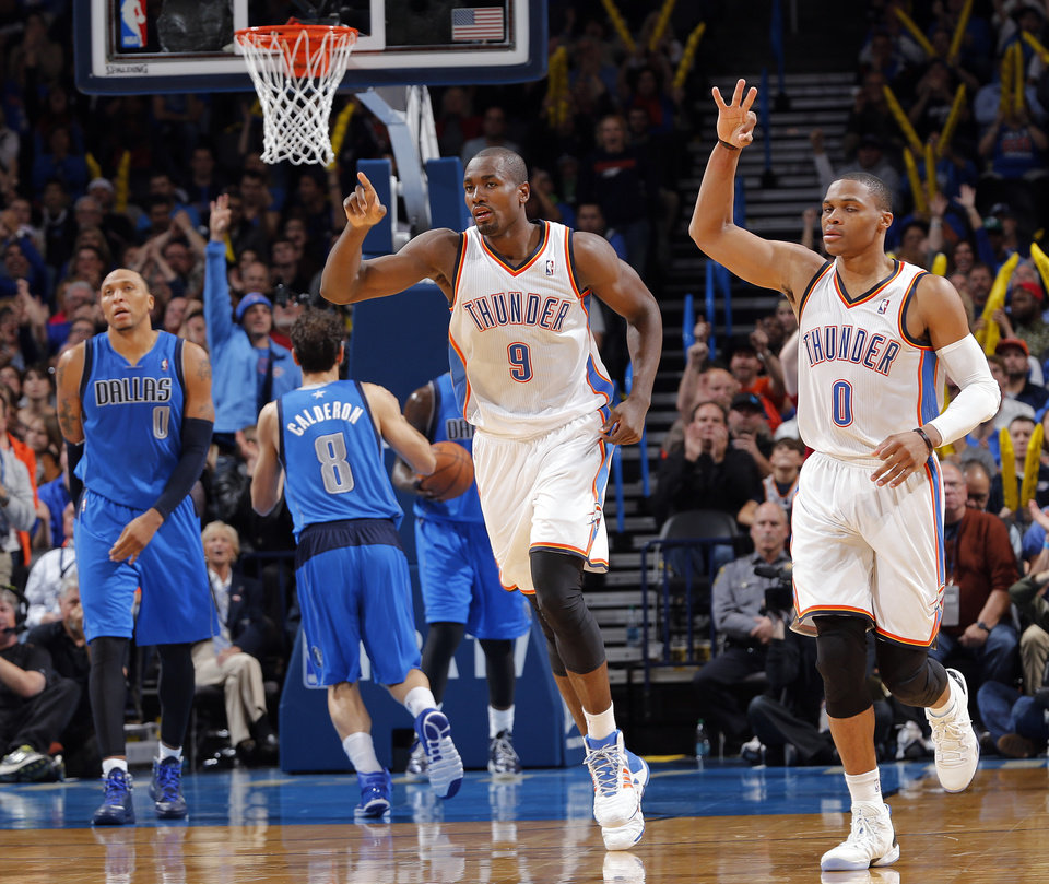 Photo - Oklahoma City's Serge Ibaka (9) and Russell Westbrook (0) react after a Thunder three point shot during the NBA basketball game between the Oklahoma City Thunder and the Dallas Mavericks at Chesapeake Energy Arena in Oklahoma City, Okla. on Wednesday, Nov. 6, 2013.  Photo by Chris Landsberger, The Oklahoman
