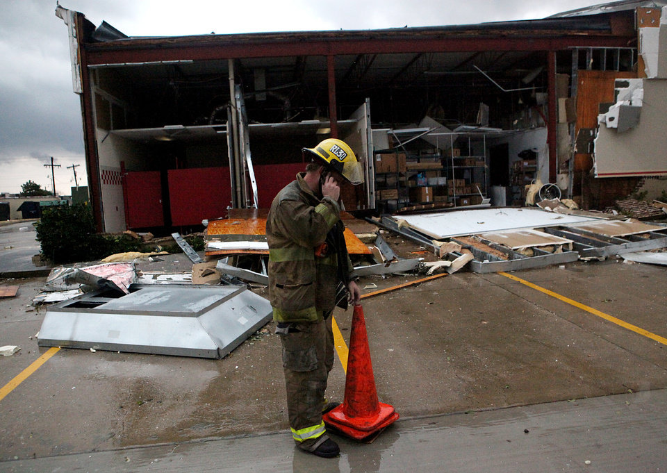 Photo - A firefighter talks on a cell phone in front of damage to the Chuck E Cheese restaurant following storms near NW Expressway and Rockwell  in Oklahoma City on Tuesday, Feb. 10, 2009. By John Clanton, The Oklahoman