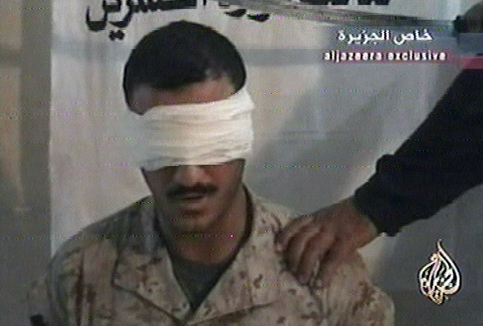 Photo - FILE - This June 27, 2004, file image from a video broadcast by the Al-Jazeera network, shows a man identified as US Marine Cpl. Wassef Ali Hassoun. Nearly 10 years ago Hassoun was declared a deserter after allegedly faking his own kidnapping in Iraq, then reappeared and was to face charges. But he disappeared again in 2005, has now turned himself in to U.S. authorities, and is being flown to the U.S. Sunday, June 29, 2014, from an undisclosed Mideast location. Once at Camp Lejeune, the commander of the 2nd Marine Expeditionary Force will determine whether to court-martial him.  (AP Photo/ Al-Jazeera via APTN)