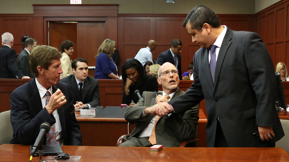 Photo - George Zimmerman, right, greets his defense counsel, Mark O'Mara, left, and Don West, as they arrive in court to hear a jury question, on the 25th day of Zimmerman's trial at the Seminole County Criminal Justice Center in Sanford, Fla., Saturday, July 13, 2013. Zimmerman has been charged with second-degree murder the 2012 shooting death of Trayvon Martin. (AP Photo/Joe Burbank, Pool) ORG XMIT: FLJR224
