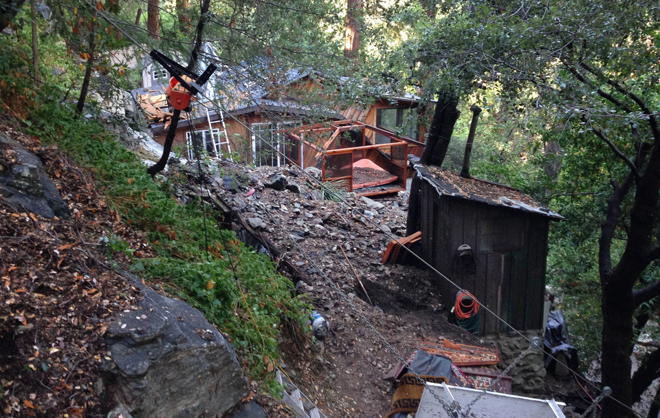 Photo - Debris and rocks are piled up outside a cabin in Bear Canyon in Mount Baldy, Calif., Monday, Aug. 4, 2014, after thunderstorms Sunday caused mountain mudslides in Southern California. Authorities estimated that between 6 and 8 homes were badly damaged and likely uninhabitable. (AP Photo/Brian Melley)