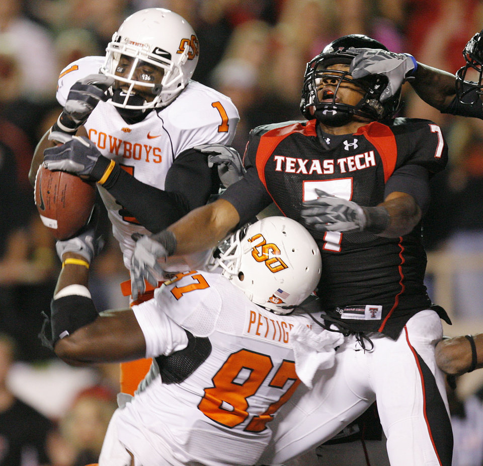 Photo - Oklahoma State's Dez Bryant (1) and Brandon Pettigrew (87) battle for a ball against Texas Tech's Darcel McBath (7) during the first half of the college football game between the Oklahoma State University Cowboys (OSU) and the Texas Tech Red Raiders at Jones AT&T Stadium on Saturday, Nov. 8, 2008, in Lubbock, Tex.BY CHRIS LANDSBERGER/THE OKLAHOMAN