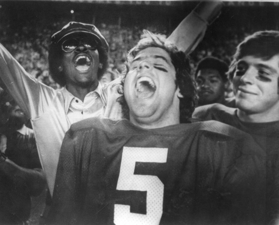 COLLEGE FOOTBALL: 1976 ORANGE BOWL -- SOONER QB STEVE DAVIS, CENTER, AND AN OU FAN START CELEBRATING AS TIME RUNS OUT WHILE A SMILING TEAMMATE, DEAN BLEVINS, LOOKS ON