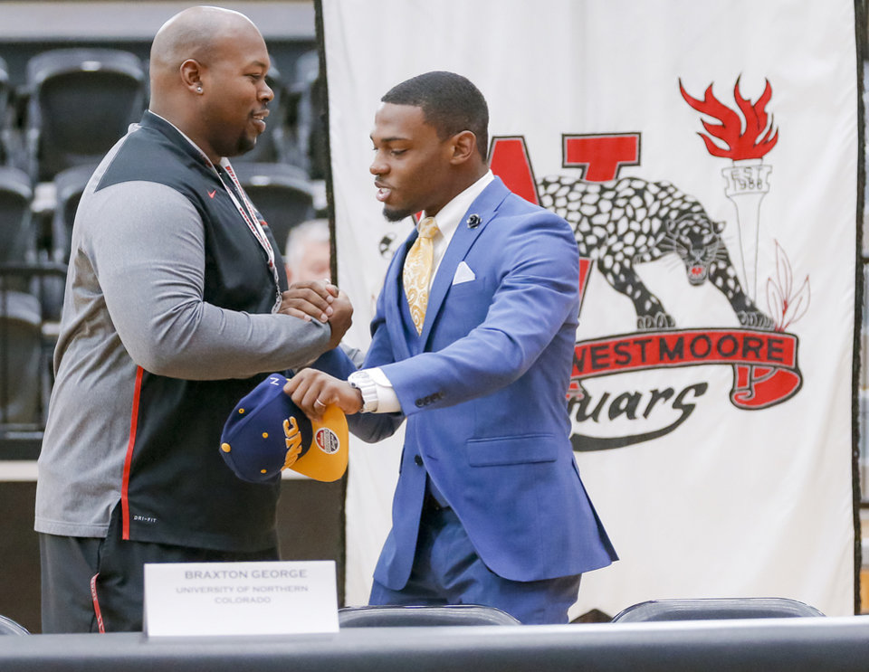 Photo - Westmoore's Braxton George shakes hands with football coach Lorenzo Williams before he signs his letter of intent to play football for the University of Northern Colorado during national signing day at Westmoore High School in Moore, Okla. on Wednesday, Feb. 7, 2018.  Photo by Chris Landsberger, The Oklahoman