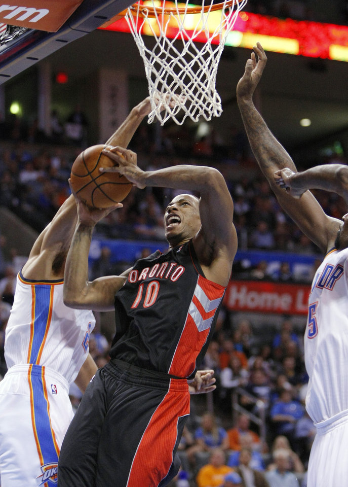 Toronto Raptors guard DeMar DeRozan, center, goes up for a shot between Oklahoma City Thunder guard Thabo Sefolosha, left, and center Kendrick Perkins during the first quarter of an NBA basketball game in Oklahoma City, Tuesday, Nov. 6, 2012. (AP Photo/Alonzo Adams)
