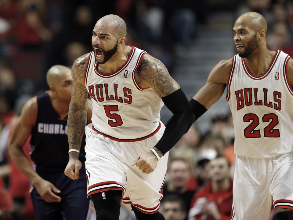 Chicago Bulls forward Carlos Boozer (5), reacts after scoring against the Charlotte Bobcats next to Chicago Bulls forward Taj Gibson (22) during the first half of an NBA basketball game in Chicago, Saturday, Jan. 11, 2014. (AP Photo/Kamil Krzaczynski)
