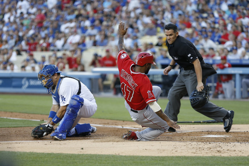 Photo - Los Angeles Angels' Howie Kendrick, center, scores past Los Angeles Dodgers catcher A.J. Ellis, left, as home plate umpire Manny Gonzalez, right, looks to make the call on a single by Angels' David Freese during the first inning of a baseball game, Monday, August 4, 2014, in Los Angeles. (AP Photo/Danny Moloshok)