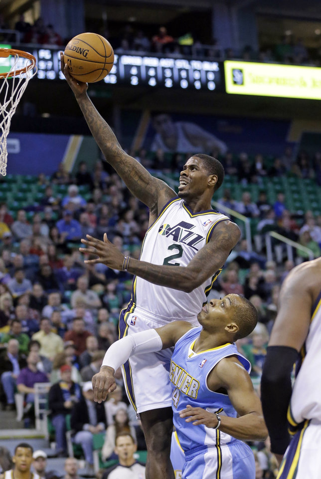 Photo - Utah Jazz's Marvin Williams (2) goes to the basket as Denver Nuggets' Randy Foye (4) defends in the first quarter during an NBA basketball game Monday, Jan. 13, 2014, in Salt Lake City. (AP Photo/Rick Bowmer)