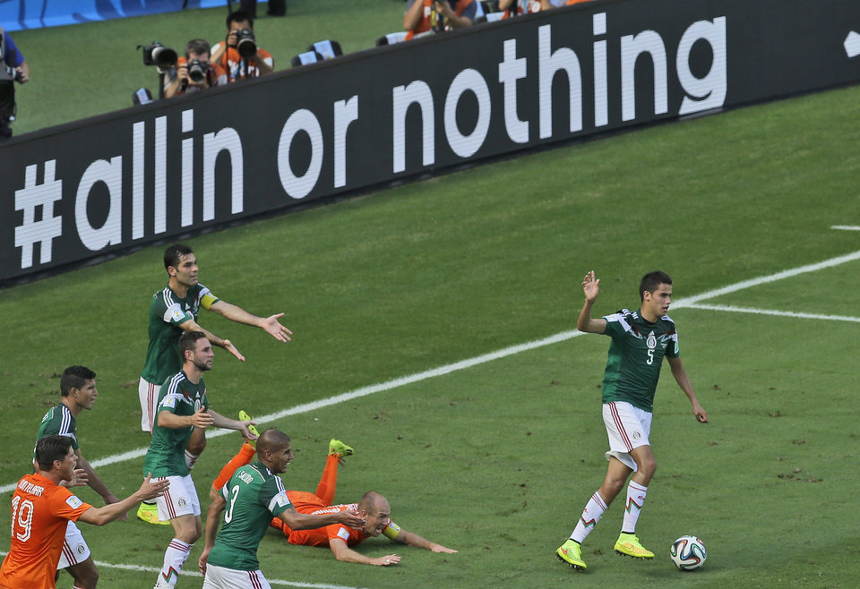 Photo - Mexico's Rafael Marquez, left, gestures after fouling Netherlands' Arjen Robben inside the penalty zone during the World Cup round of 16 soccer match between the Netherlands and Mexico at the Arena Castelao in Fortaleza, Brazil, Sunday, June 29, 2014. (AP Photo/Themba Hadebe)