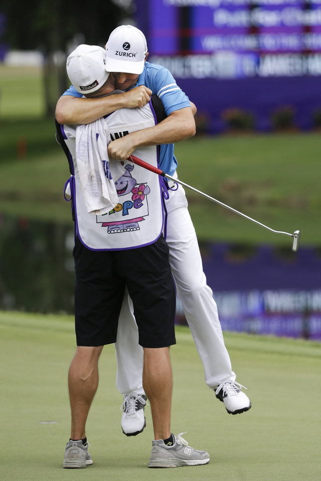 Photo - Ben Crane, rear,  hugs his caddie, Joel Stock, on the 18th green after Crane won the St. Jude Classic golf tournament Sunday, June 8, 2014, in Memphis, Tenn. Crane won the tournament with a score of 10-under 270.(AP Photo/Mark Humphrey)