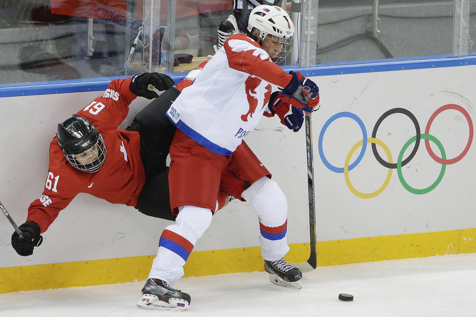 Photo - Alyona Khomich of Russia pins Romy Eggimann of Switzerland up against the boards during the 2014 Winter Olympics women's ice hockey quarterfinal game at Shayba Arena, Saturday, Feb. 15, 2014, in Sochi, Russia. (AP Photo/Matt Slocum)