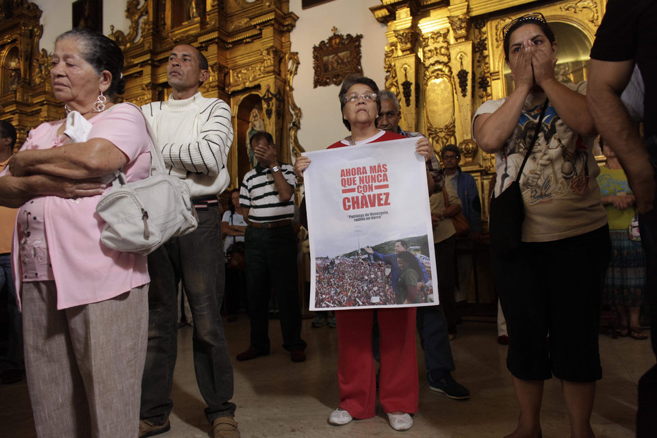 "People, one of them holding an image of Venezuela's President Hugo Chavez That reads in Spanish ""Now more than ever with Chavez,"" gather to pray for him at a church in Caracas, Venezuela, Monday, Dec. 31, 2012. Venezuela's President Hugo Chavez is confronting ""new complications"" due to a respiratory infection nearly three weeks after undergoing cancer surgery, his Vice President Nicolas Maduro said Sunday evening in Cuba as he visited the ailing leader for the first time since his operation. (AP Photo/Ariana Cubillos)"