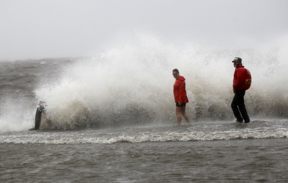 Photo -   A man sits on the seawall as his friends walk in the storm surge from Isaac, on Lakeshore Drive along Lake Pontchartrain, as the storm approaches landfall, in New Orleans, Tuesday, Aug. 28, 2012. (AP Photo/Gerald Herbert)