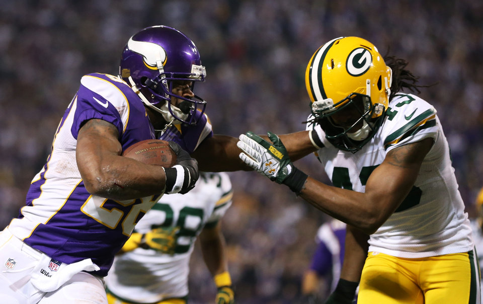 Photo - Minnesota Vikings running back Adrian Peterson, left, tries to break a tackle by Green Bay Packers free safety M.D. Jennings, right, during the second half of an NFL football game Sunday, Dec. 30, 2012, in Minneapolis. (AP Photo/Jim Mone)