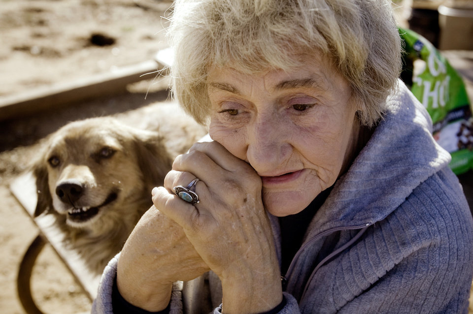 Photo - Catherine Titus sits on a park bench with one of the 100 plus dogs she care for on Tuesday, Dec. 30, 2008, in Wilson, Okla. Titus who live out of a broken down van with no running water or electricity spends most all of her monthly $700 Social Security check to care for the dogs she calls her best friends.  Titus makes sure the dogs are fed twice a day, and are also given dog treats as a little something extra.