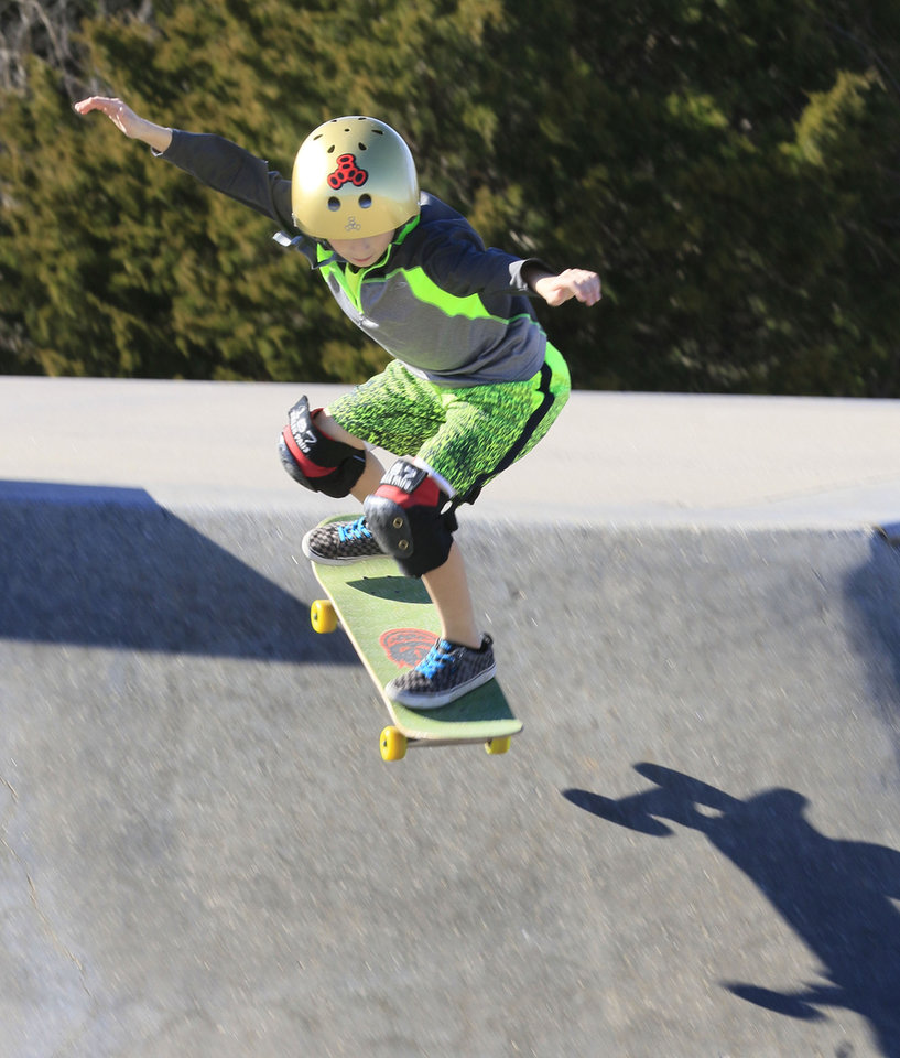 Photo -  T. J. Cooper, 9, flies over the edge with his skateboard. [PHOTO BY PAUL HELLSTERN, THE OKLAHOMAN]