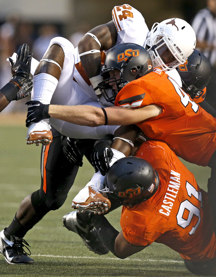 Photo - Oklahoma State's James Castleman (91) and Oklahoma State's Caleb Lavey (45) bring down Texas' Joe Bergeron (24) during a college football game between Oklahoma State University (OSU) and the University of Texas (UT) at Boone Pickens Stadium in Stillwater, Okla., Saturday, Sept. 29, 2012. Photo by Bryan Terry, The Oklahoman