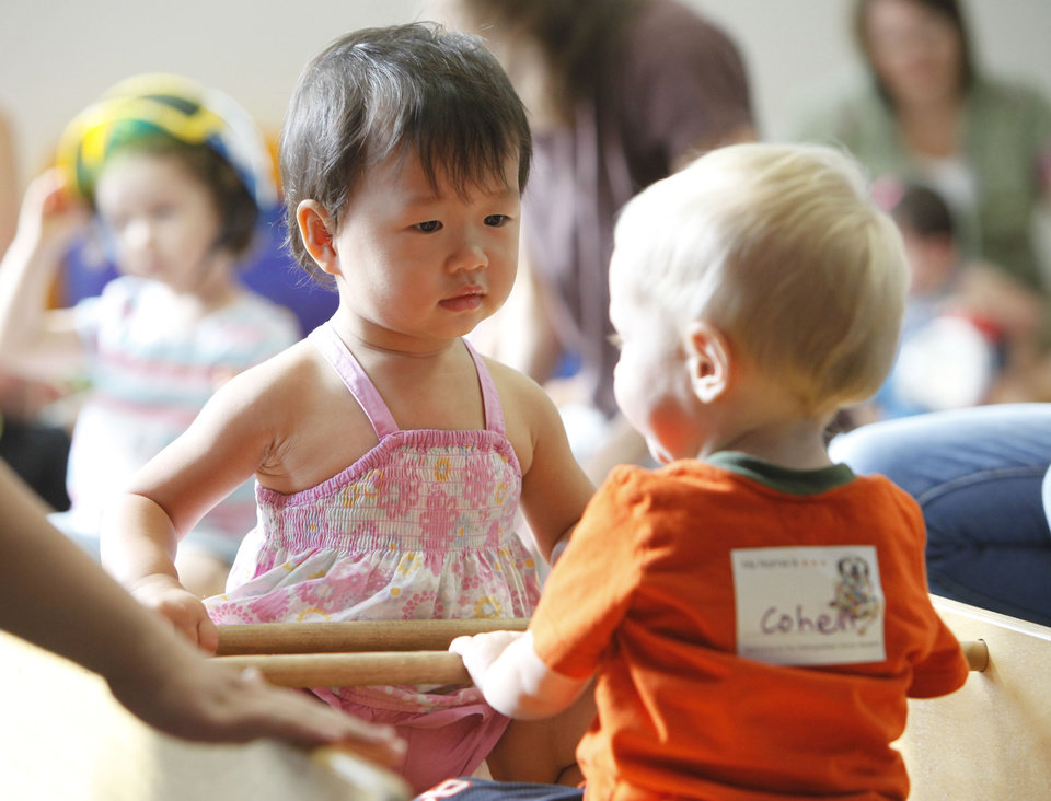 "18-month-old Joy Zhai and one-year-old Cohen Colwell play on a see-saw during ""Playtime for Toddlers"" at the Edmond Library in Edmond, OK, Tuesday, Aug. 31, 2010. By Paul Hellstern, The Oklahoman"