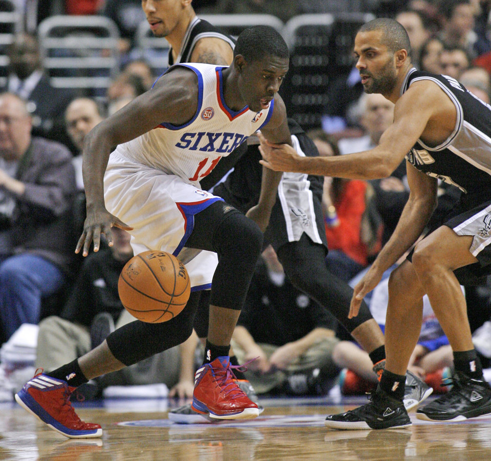 Philadelphia 76ers' Jrue Holiday (11) drives against San Antonio Spurs' Tony Parker during the first half of an NBA basketball game Monday Jan. 21, 2013, in Philadelphia. (AP Photo H. Rumph Jr)