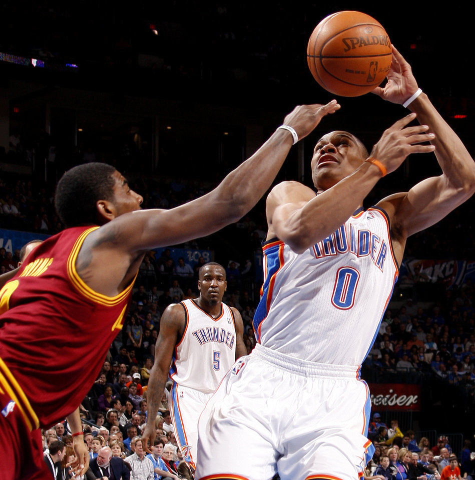 Photo - Oklahoma City's Russell Westbrook (0) tries to gain control of the ball beside Cleveland's Kyrie Irving (2) during the NBA basketball game between the Oklahoma City Thunder and the Cleveland Cavaliers at Chesapeake Energy Arena in Oklahoma City, Friday, March 9, 2012. Photo by Bryan Terry, The Oklahoman
