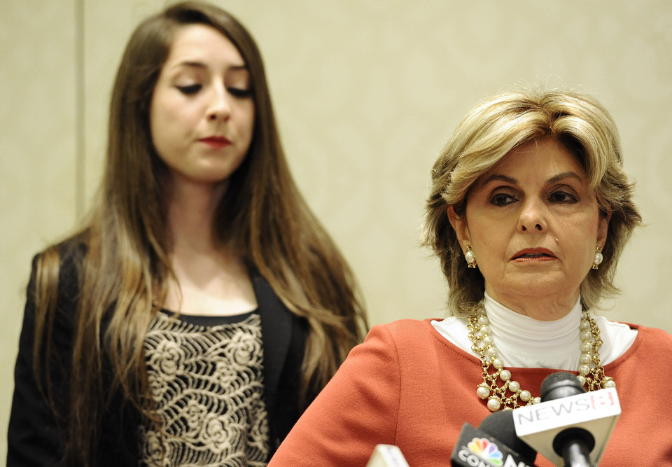 Photo - Attorney Gloria Allred, speaks to the media as former University of Connecticut student Carolyn Luby, left, listens, during a news conference, Friday, July 18, 2014. The University of Connecticut will pay nearly $1.3 million to settle a federal lawsuit filed by five women who claimed the school responded to their sexual assault complaints with indifference, the two sides announced Friday.  (AP Photo/Jessica Hill)