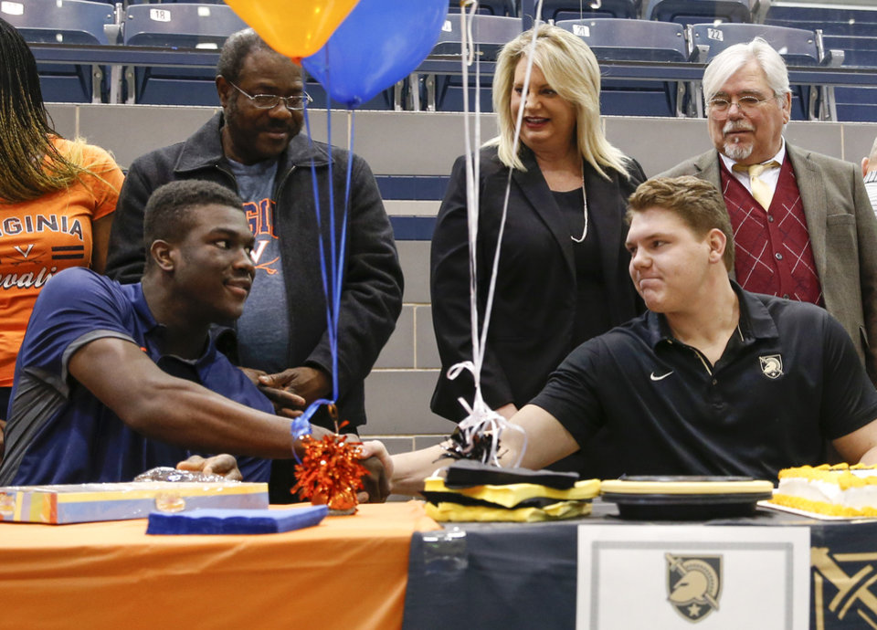 Photo - Daryl Dike, left, and Hunter Richard shake hands during a ceremony for National Signing Day at Edmond North High School in Edmond, Okla., Wednesday, Feb. 7, 2018. Behind Dike is his father, Vincent Dike, and behind Richard are his parents, Jennifer Richard and Bert Richard. Dike signed to play soccer at Virginia. Richard will play football at Army West Point. Photo by Nate Billings, The Oklahoman