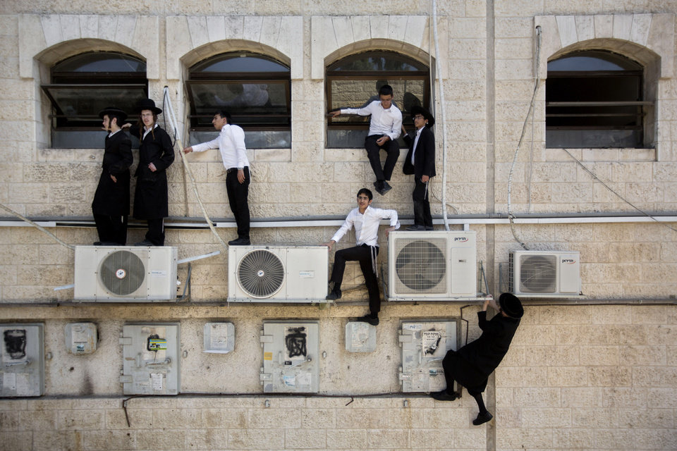Photo - AP10ThingsToSee - Ultra-Orthodox Jewish boys climb a wall to watch the scene of an attack in Jerusalem, Monday, Aug. 4, 2014. (AP Photo/Sebastian Scheiner)