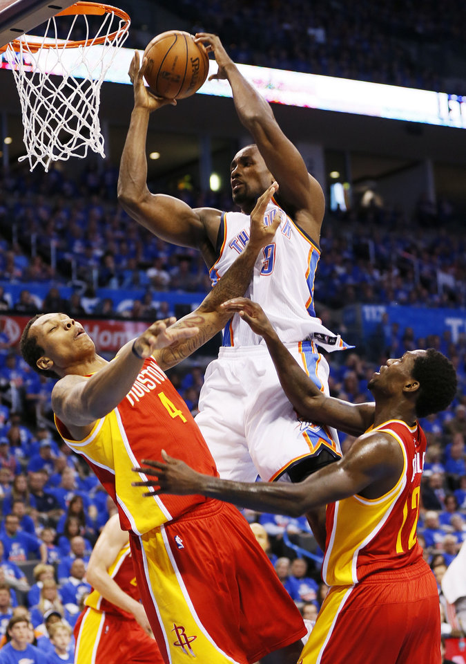 Oklahoma City\'s Serge Ibaka (9) grabs a rebound between Houston\'s Greg Smith (4) and Patrick Beverley (12) in the second half during Game 5 in the first round of the NBA playoffs between the Oklahoma City Thunder and the Houston Rockets at Chesapeake Energy Arena in Oklahoma City, Wednesday, May 1, 2013. Houston won, 107-100. Photo by Nate Billings, The Oklahoman