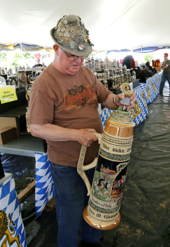 Photo - Bavarian Gift Haus owner R. D. Diener shows an enormous beer stein during the annual Oktoberfest celebration in Choctaw, Okla. Monday, Sept. 5, 2016.  Photo by Paul Hellstern, The Oklahoman