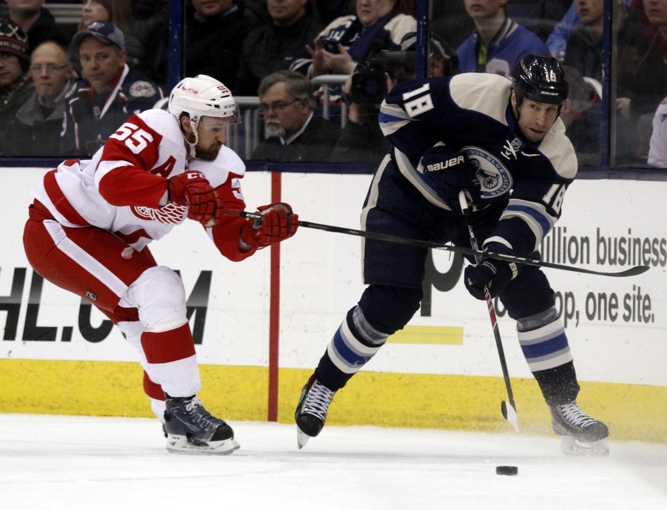 Photo - Columbus Blue Jackets' R.J. Umberger , right, passes the puck in front of Detroit Red Wings' Niklas Kronwall, of Sweden, in the first period of an NHL hockey game in Columbus, Ohio, Tuesday, March 25, 2014. (AP Photo/Paul Vernon)