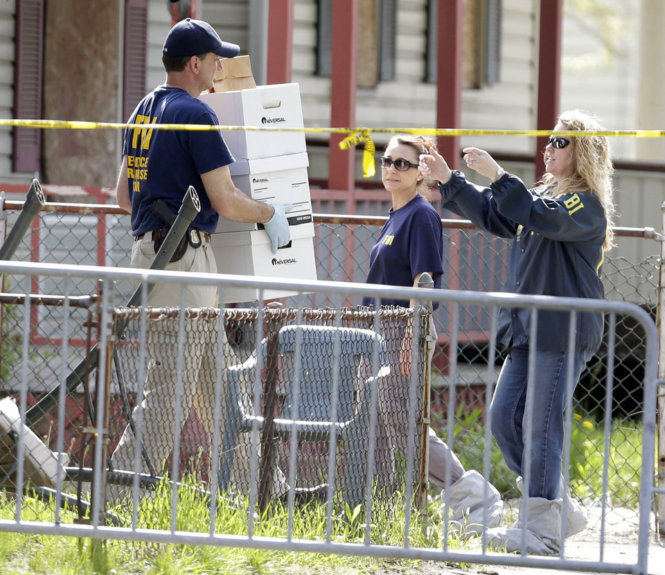Photo - Law enforcement officials gather evidence at the crime scene where three women were held captive  in Cleveland, Ohio, Thursday, May 9, 2013.  Ariel Castro, a 52-year-old former school bus driver, is being held on $8 million bail under a suicide watch in jail, where he is charged with rape and kidnapping for allegedly abducting three women and holding them captive in his home for a decade.  (AP Photo/David Duprey)
