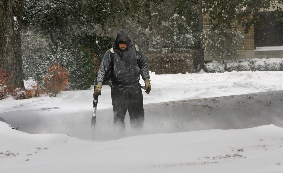 Photo - City employee Philip Brooks uses a leaf blower to clear snow near the Municipal Complex as the second round of snow in a week moved into the area on Wednesday, February 9, 2011, in Norman, Okla. Photo by Steve Sisney, The Oklahoman