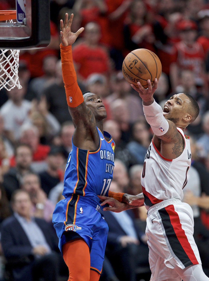 Photo - Portland Trail Blazers guard Damian Lillard, right, shoots over Oklahoma City Thunder guard Dennis Schroder during the second half of Game 2 of an NBA basketball first-round playoff series Tuesday, April 16, 2019, in Portland, Ore. (AP Photo/Craig Mitchelldyer)
