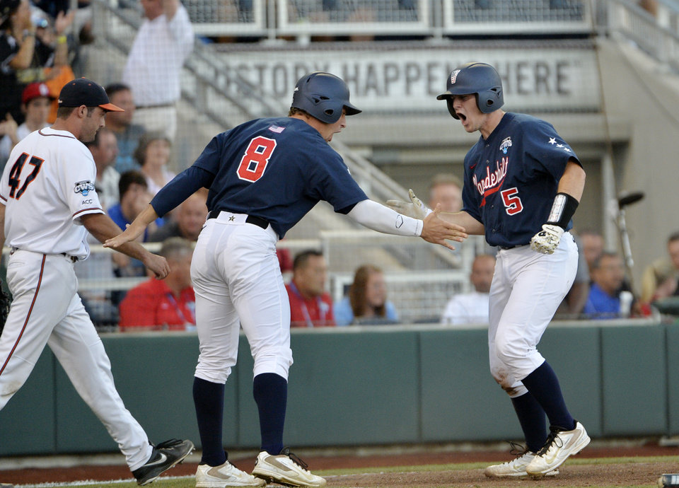 Photo - Vanderbilt catcher Jason Delay (5) celebrates with right fielder Rhett Wiseman (8) after scoring a run in the third inning of the opening game of the best-of-three NCAA baseball College World Series finals against Virginia in Omaha, Neb., Monday, June 23, 2014. (AP Photo/Ted Kirk)
